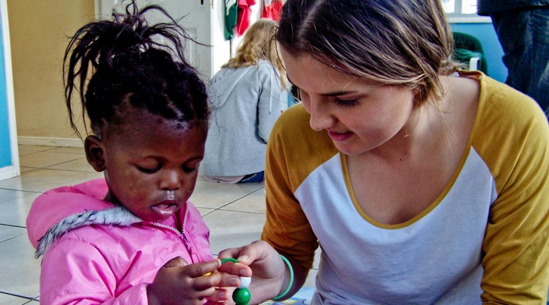 Projects Abroad Childcare volunteer helps a young child withs crafts in South Africa.